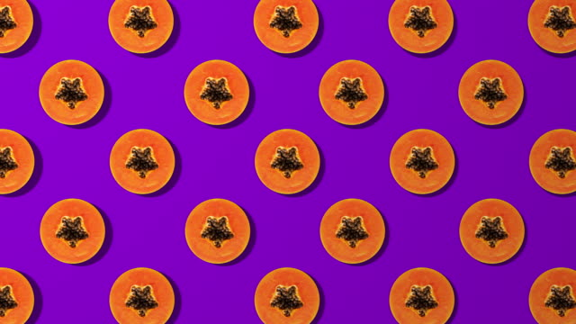 Papaya slice spinning pattern on purple background