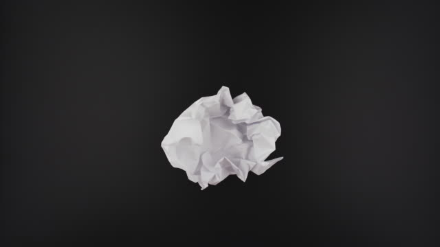 Paper ball unwrapping on black background Stop motion VDO, paper ball unwrapping on black background. torn stock videos & royalty-free footage