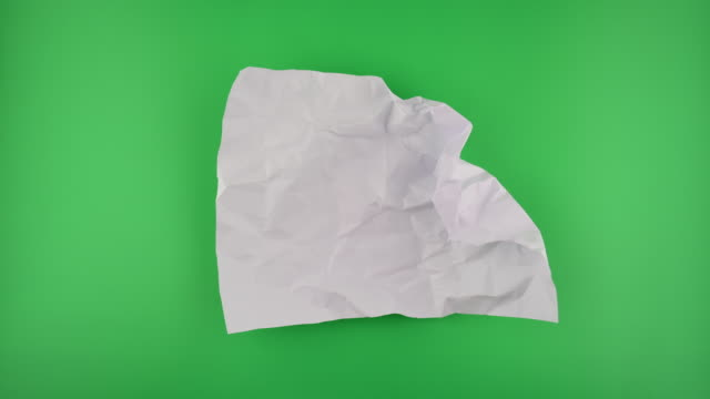 Paper ball unwrapping on green background.
