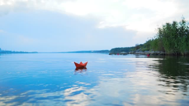 A paper boat floating away into the distance.