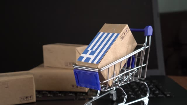 paper box with a flag of greece in a shopping cart on a laptop keyboard - grecia stato video stock e b–roll