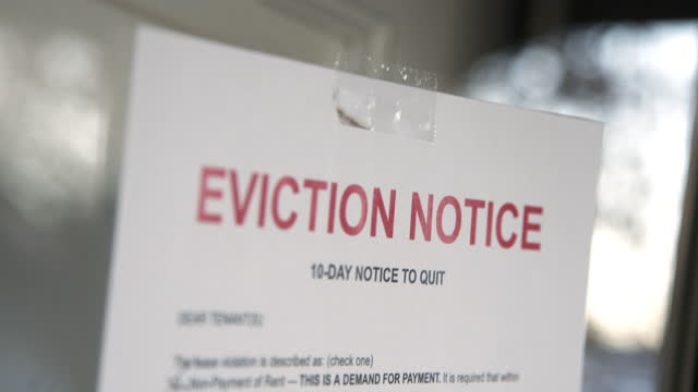 Paper Eviction Notice Taped to the Front Door of a Rental Home in a Residential Suburban Neighborhood 10-Day Notice to Quit Paper sign foreclosure stock videos & royalty-free footage