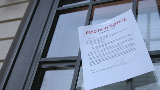Paper Eviction Notice Taped to the Front Storm Door of a Rental Home in a Residential Suburban Neighborhood 10-Day Notice to Quit Paper sign foreclosure stock videos & royalty-free footage