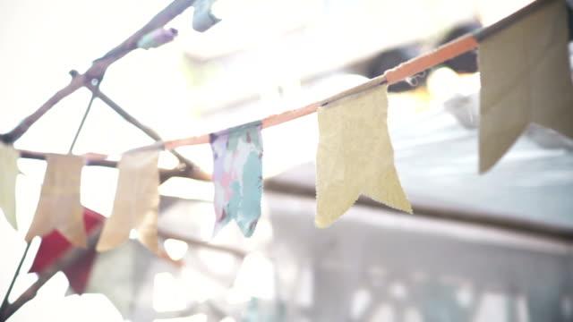 vídeos de stock, filmes e b-roll de bandeiras de papel pendurado com corda para festa ao ar livre. - estilo de vida dos abastados