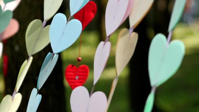 vidéos et rushes de coeurs de papier sur une chaîne se balançant dans le vent. décoration coeurs. - rendez vous amoureux