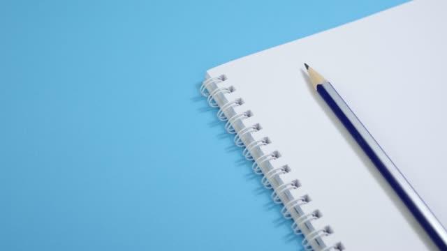 vídeos de stock e filmes b-roll de paper notepad with pencil on blue background - caneta