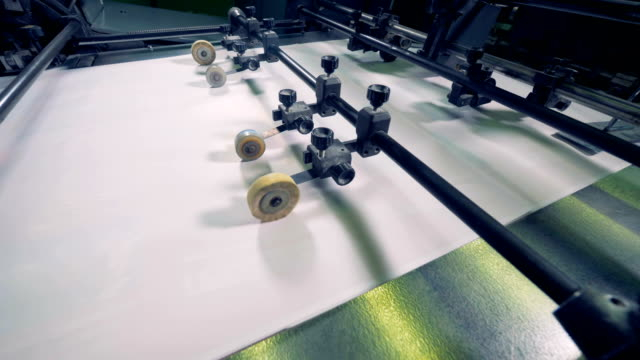 paper production machine. processing of secondary resources. machine rollers move paper on a conveyor, close up. - мембрана клетки стоковые видео и кадры b-roll