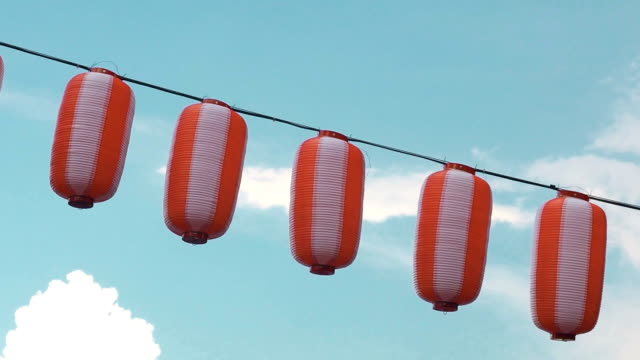 paper red-white japanese lanterns chochin hanging on blue cloudy sky background - японский фонарь стоковые видео и кадры b-roll