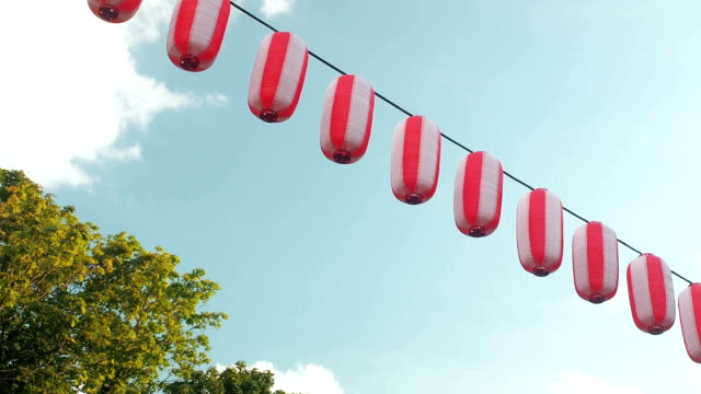 paper red-white japanese lanterns chochin hanging on blue sky background and trees - японский фонарь стоковые видео и кадры b-roll