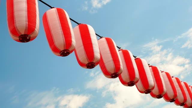 rot-weiße japanische papierlaternen chochin hängen auf blauen himmelshintergrund - tradition stock-videos und b-roll-filmmaterial
