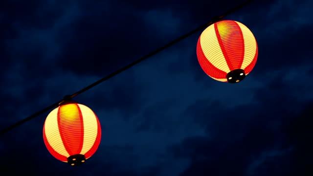 paper red-white japanese lanterns chochin shines on dark sky - японский фонарь стоковые видео и кадры b-roll