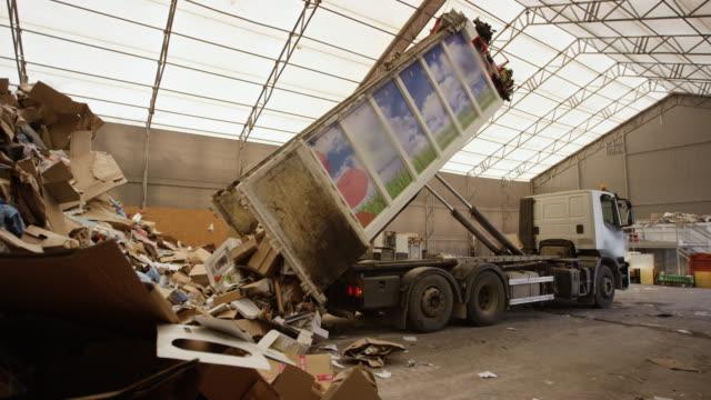 vídeos de stock e filmes b-roll de paper trash being unloaded at recycling factory - economia circular