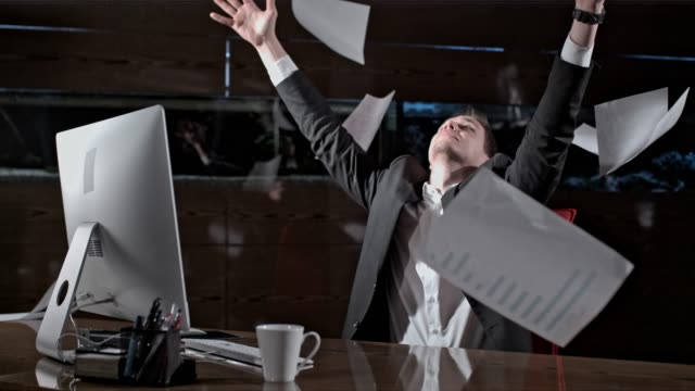 Paperwork falling over carefree businessman working late at office desk, super slow motion