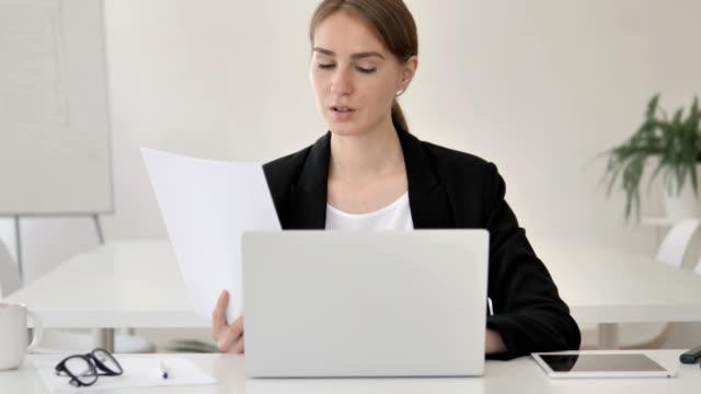 papierkrain, junge geschäftsfrau, die an dokumenten und laptop arbeitet - formelle geschäftskleidung stock-videos und b-roll-filmmaterial