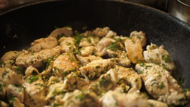Paprika ground pepper and salt pour on stewed chicken breast in cast-iron frypan video