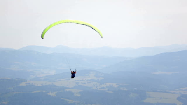 Paraglider flies over the mountains video