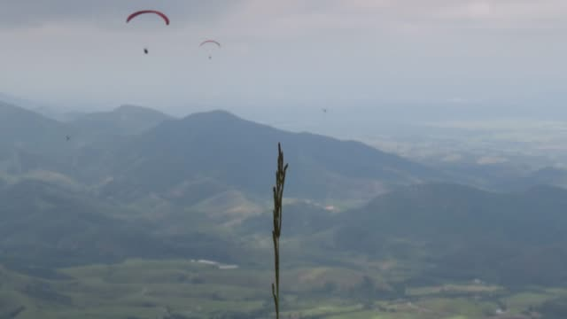 Paraglider flight over the mountains on a cloudy day