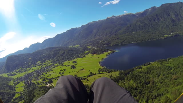 pov: paraglider flying above gorgeous countryside between mountains on sunny day - парапланеризм стоковые видео и кадры b-roll