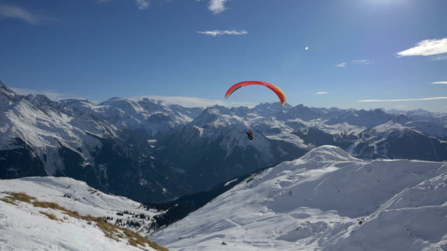 Paraglider flying above mountains