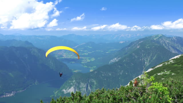 paraglider over mountains and lkes. uhd - парапланеризм стоковые видео и кадры b-roll