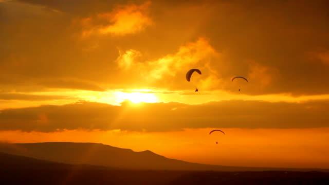parapendio al largo silhouette al tramonto - volo con parapendio video stock e b–roll