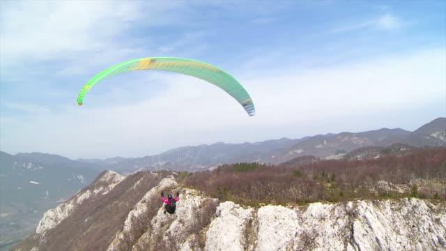 hd: параглайдер высокими на горы - парапланеризм стоковые видео и кадры b-roll
