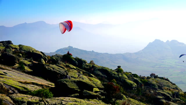 paraglider takes off mountain during paragliding extreme sport competition - парапланеризм стоковые видео и кадры b-roll