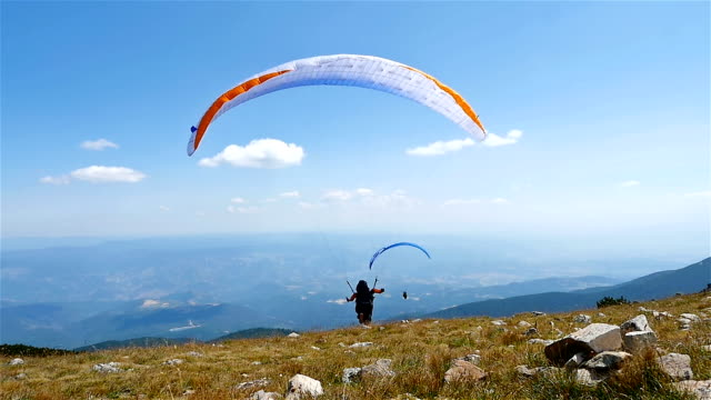 paragliders fly over amazing mountain, slow motion - парапланеризм стоковые видео и кадры b-roll