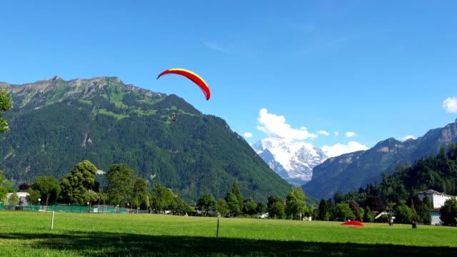 INTERLAKEN, Schweiz: Gleitschirme vor den Alpen in Interlaken, Schweiz. Interlaken ist ein Kurort im Landkreis Interlaken-Oberhasli im Kanton Bern. – Video