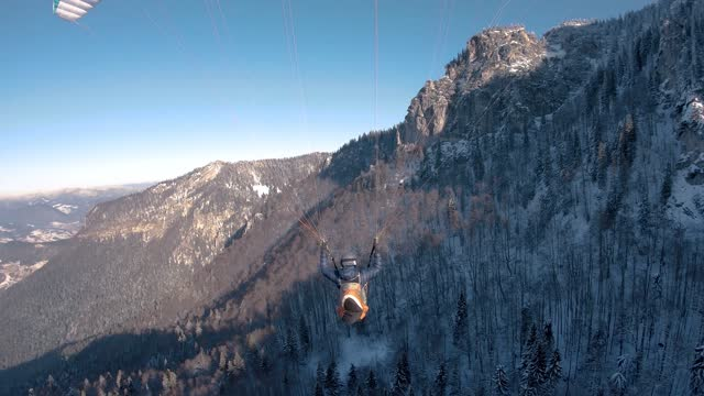 Paragliding flight above winter forest mountains nature, Freedom fly adrenaline adventure Follow cam