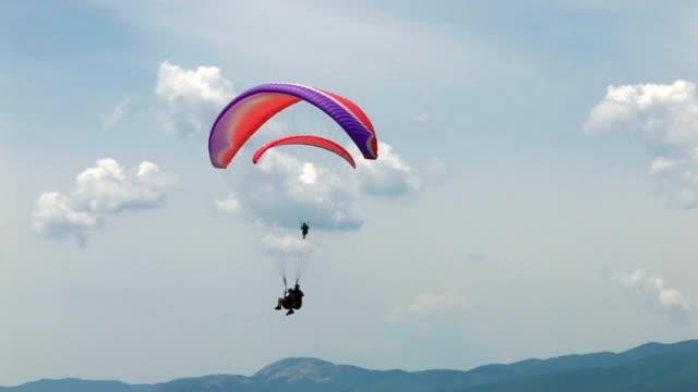 hd parapendio nel cielo blu - volo con parapendio video stock e b–roll