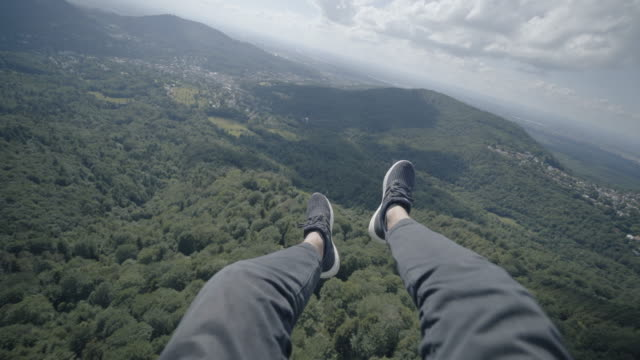 POV paragliding over forest and towns