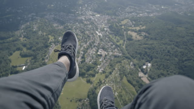 pov paragliding over forest and towns - парапланеризм стоковые видео и кадры b-roll