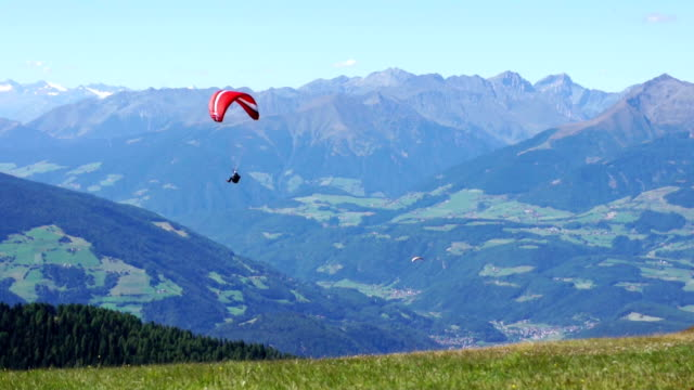 Paragliding over the mountains against clear blue sky, Kronplatz, Italy