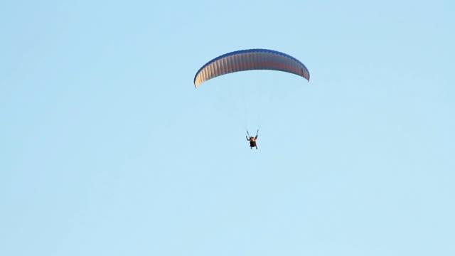 parapendio sopra le montagne contro chiaro cielo blu - volo con parapendio video stock e b–roll