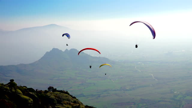 paragliding over the mountains against clear blue sky - парапланеризм стоковые видео и кадры b-roll