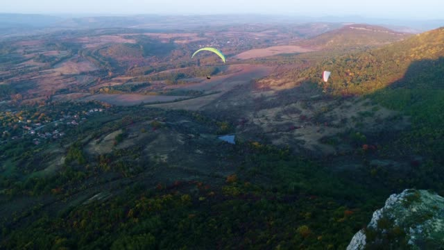 ws pan pov paragliding pilot in the mid-air, flying, cross country pilot, extreme sports, adventure - парапланеризм стоковые видео и кадры b-roll