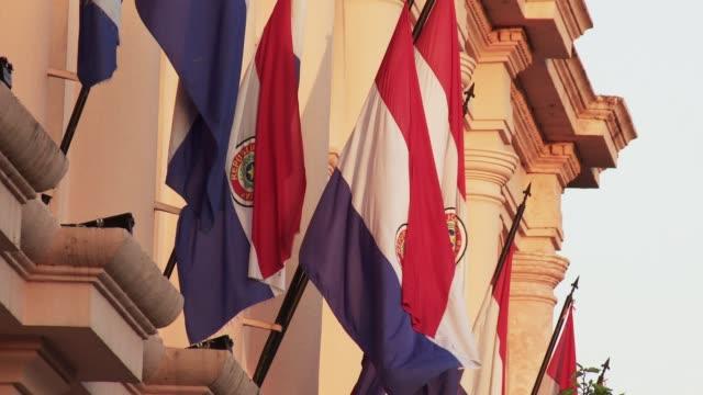 paraguayan flags waving in a building of asuncion, paraguay. - парагвай стоковые видео и кадры b-roll