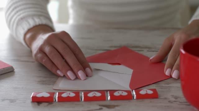 ラブノートを開く認識できない女性の視差ショット - バレンタイン チョコ点の映像素材/bロール
