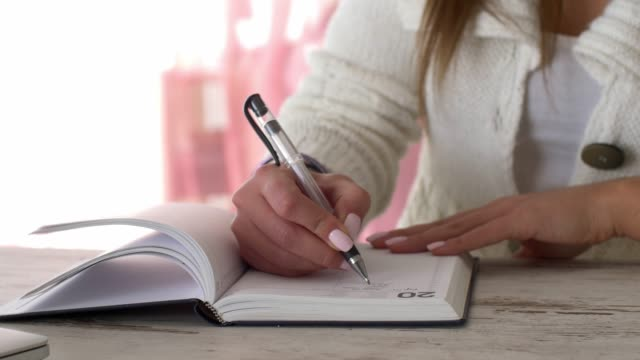 parallax shot of unrecognizable young female writing to do list in her diary - to do list video stock e b–roll