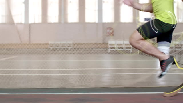 Paralympic Athlete Running with Animated Physical Metrics Projections Tracking shot of paralympic athlete with prosthetic leg running on track; digitally animated pulse and speed projections appearing on his knee and hip amputee stock videos & royalty-free footage