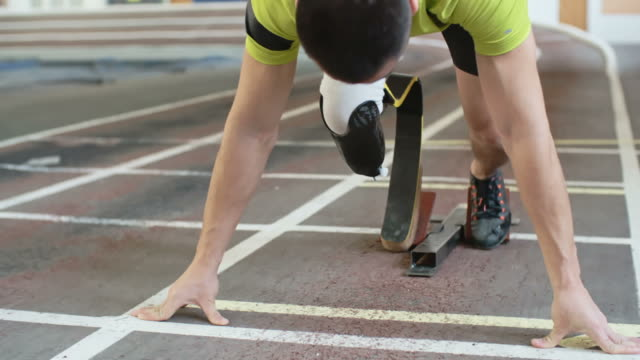Paralympic Athletestarting From Blocks Young athlete with artificial leg starting from blockson track in slow motion amputee stock videos & royalty-free footage