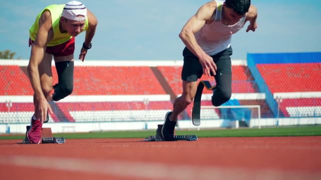 パラリンピックランナーがスタジアムでジョギングを始める - disabilitycollection点の映像素材/bロール
