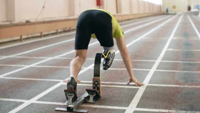 ParalympicRunner Starting a Race Rear view of athlete with artificial leg starting from blocksin slow motion prosthetic equipment stock videos & royalty-free footage