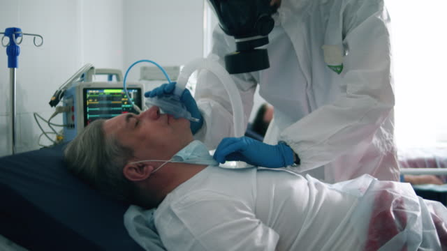 Paramedic is putting an oxygen mask on a male patient. Coronavirus, covid-19 infected patients in a clinic. video