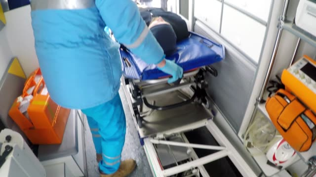 pov of paramedic loading patient on stretcher into ambulance - first responders стоковые видео и кадры b-roll