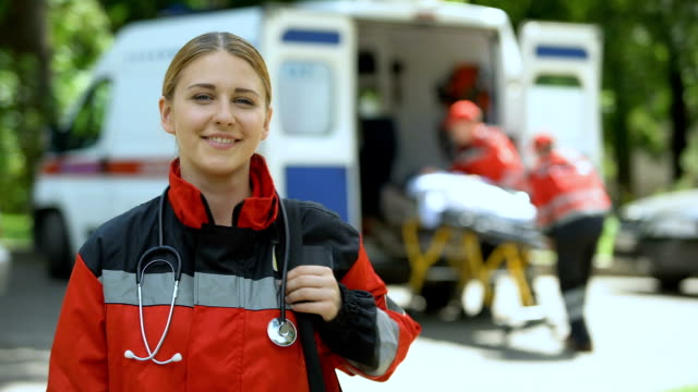 Paramedic posing for camera, ambulance crew transporting patient to clinic video
