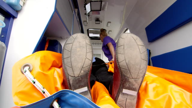 Paramedic provide emergency medical care for senior patient in ambulance video