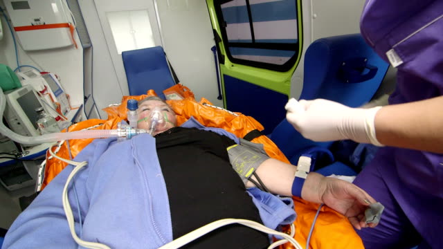 Paramedic provide emergency medical care to patient in ambulance preparing drip video
