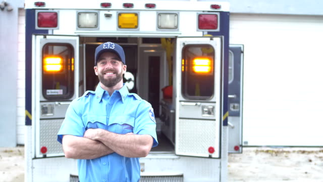 Paramedic standing in front of ambulance A young man in his 20s working as a paramedic, standing with his arms crossed in front of the back of an ambulance, smiling confidently at the camera. rescue worker stock videos & royalty-free footage